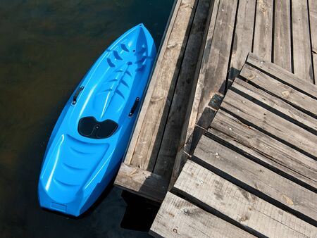 Small plastic rowing boat azure color designed for kids. Top view photo of kayak near plank pier