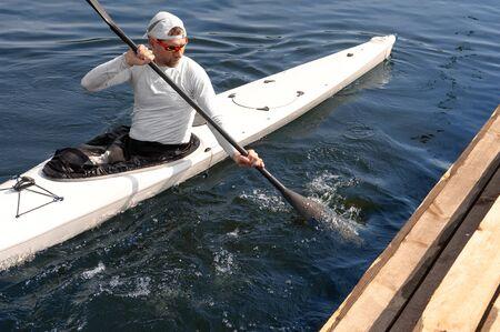 Homme pagayer un kayak blanc sur la rivière près du rivage. Concept de kayak
