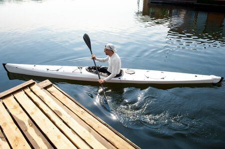 Active hobby concept. New white canoe with paddle man departing from the pier