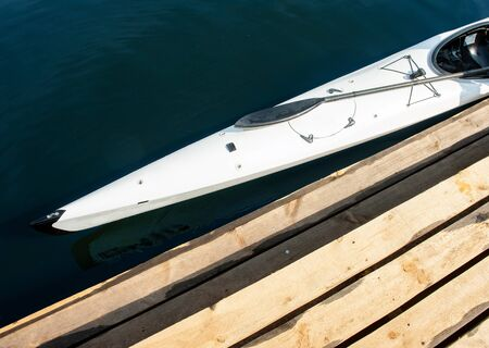 Cropped close-up photo of sportive boat. Top view of professional speed canoe placed near boardwalk pier Banque d'images