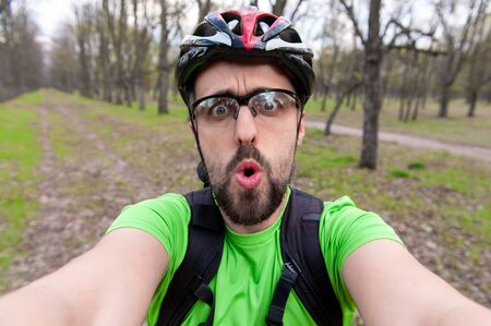 Having fun and adrenalin concept. while Surprised cyclist in protective sports glasses and helmet is training on road bike. He is taking a selfie in a beautiful landscape Banque d'images