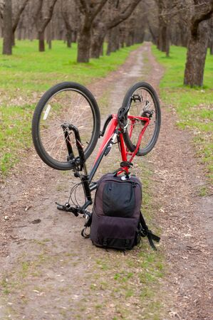 Active and sport leisure concept. Mountain bike standing up for technical checking and black photo backpack placed nearby on the ground