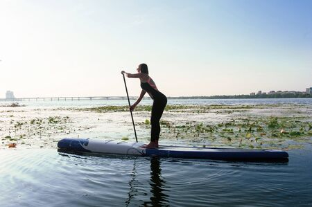 Young athletic woman doing fitness on a board with an oar on a lake. Banque d'images - 135682048