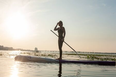 SUP silhouette of young girl paddle boarding at sunset Banque d'images