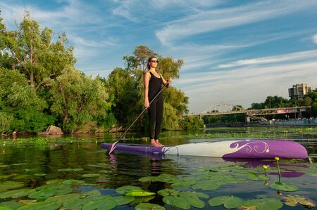 Young athletic woman doing fitness on a board with an oar on a lake. Banque d'images