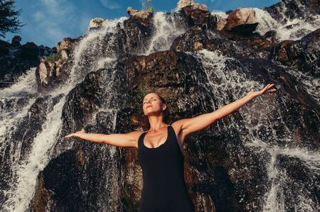 Freedom or recreation concept. Athletic woman stretching her arms with eyes closed enjoying freshness on summer day with rock and waterfall on background. Photo with copy space on top. Banque d'images