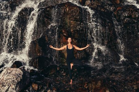 Sport and health concept. Girl in tight sportswear meditating in yoga asana on nature. She is standing on stone coast near waterfall at sunset Banque d'images