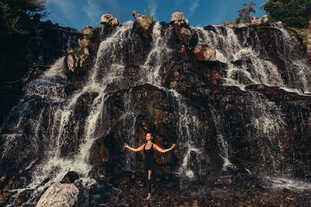 Serenity and calmness concept. Attractive active woman standing in asana, meditating at waterfall and rocky mountains with beautiful nature landscape