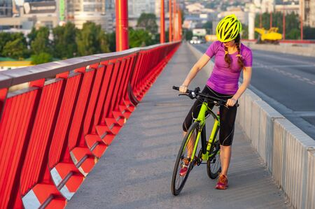 Cardio training or leisure concept. Full length portrait of sporty girl starting to move by bicycle on a straight road with bright red fence Banque d'images