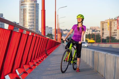 Morning workout concept. Young athletic woman made a stop during bike ride to enjoy the city in sunset view. She is wearing bright sportswear and a light green helmet Banque d'images