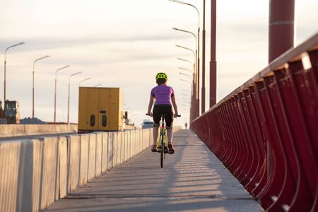 Low angle back view photo of female cyclist driving off into the distance along a bicycle path on a bridge with perspective of street lamps Banque d'images