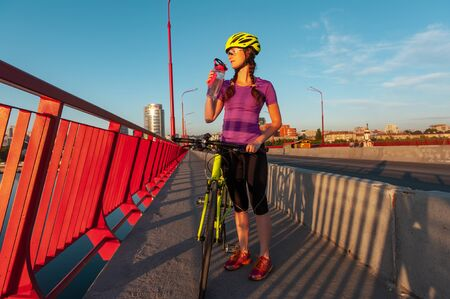 Refreshness and sport concept. Female cyclist made a stop on bridge to drink water. She is looking away and holding a sports bottle