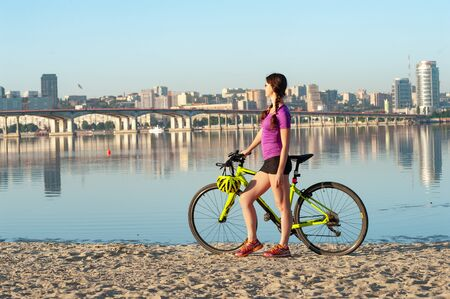Attractive sportswoman standing on sandy beach with her mountain bike and beautiful sunny city landscape with bridge and wide river on background Banque d'images