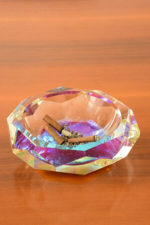 Crystal ashtray with extinct cigars on a wooden table
