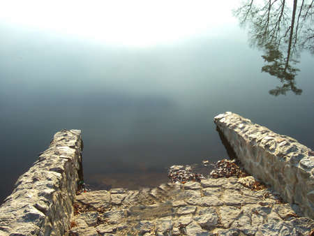 Stone steps on the embankment descend into the water, which reflects the sun and trees Stok Fotoğraf