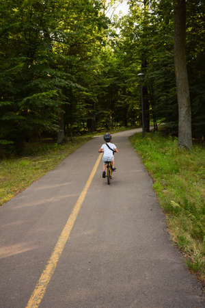 A boy on a bicycle and in a helmet rides along an asphalt path in the park