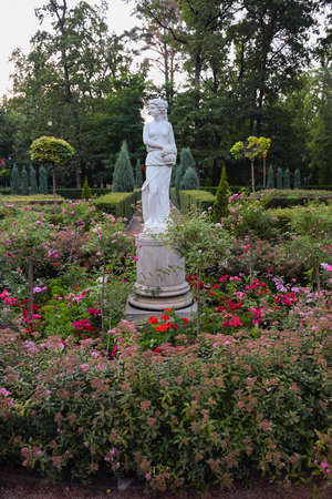 White stone statue of a girl in a summer park, near her there are many flowers, trees and greenery