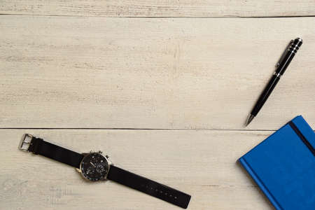 Mechanical wrist watch, diary and pen lie on a wooden table