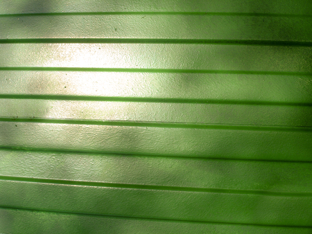 Abstract construction topic. The patches of light on the metallic green fence.
