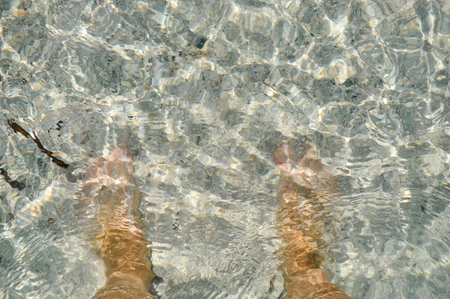 Feet in the water on the sand  Mediterranean sea, the island of Crete  Greece  photo