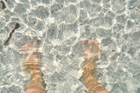Feet in the water on the sand. Mediterranean sea, the island of Crete. Greece. photo