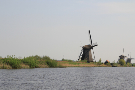 Dutch landscape with windmills. Gloomy panorama of gray water channel and windmills in Holland.
