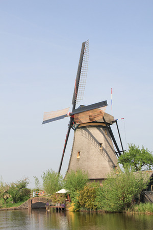 The Dutch windmill. Dutch countryside landscape with the windmill on the Bank of the canal.