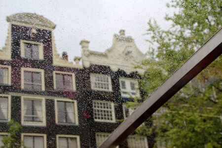 Amsterdam facades of houses through the drops of rain on the window. Cityscape Dutch capital.