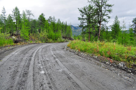 Photo dirt road after the rain in the Yakut taiga at the end of summer. Oymyakon highlands, a ridge of Suntar-khayata, between lake Ulu mosque and the river Suntar. photo