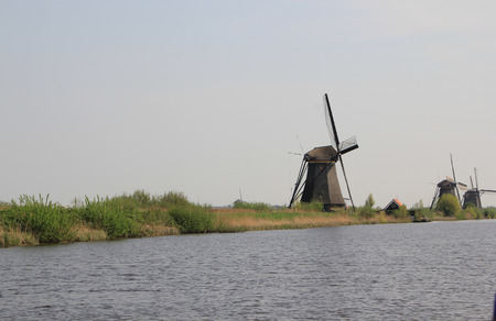 Dutch landscape with windmills  Gloomy panorama of gray water channel and windmills in Holland