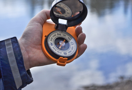 Magnetic compass in the black case on an orange ground with mirror cover to be in the hands of man  Stock Photo