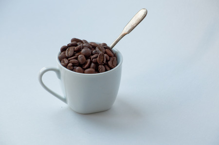 White coffee Cup, in which piled roasted coffee beans.