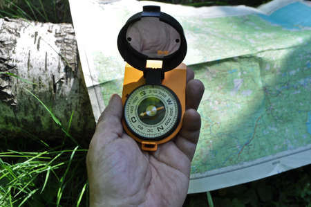 Forest, may, walk in the woods. Compass in hand, against the background of the map. Stock Photo