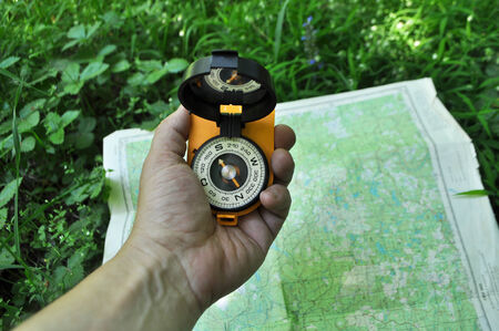 cartographer: Forest, may, walk in the woods. Compass in hand, against the background of the map. Stock Photo