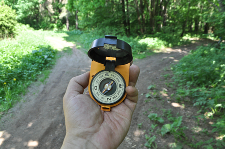 May, green forest and the path. With a compass in his hand before the fork. Archivio Fotografico