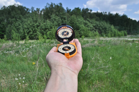 Forest, may, walk in the woods. Compass in hand, against the background of the forest. photo