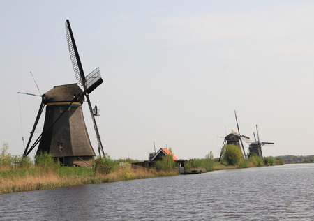 Windmills on the canal bank  Typical Dutch rural landscape in the vicinity of Amsterdam  Stock Photo