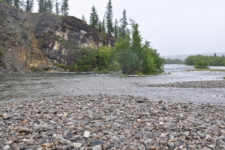 Rocky coast of Northern taiga mountain river in the area of the Polar Urals. Stock Photo
