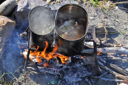 trivet: Cooking fish on the fire. Tourist fire, trivet, and two pot that cooked fish soup. Stock Photo