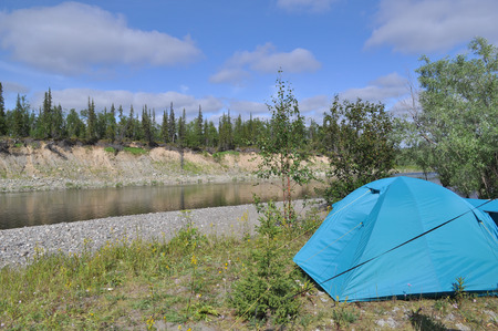 Camping tent by the river. Camping tent is located on the North river. The Polar Urals, Russia. Stock Photo