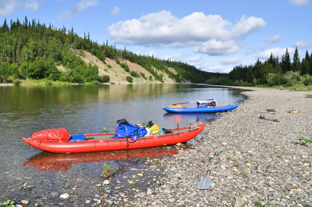 Inflatable kayaks on the shore taiga rivers. The river of the polar Urals in the Republic of Komi, Russia. Stock Photo
