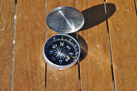 The compass on the boards. Open the magnetic compass lies on the dark wooden boards Stock Photo