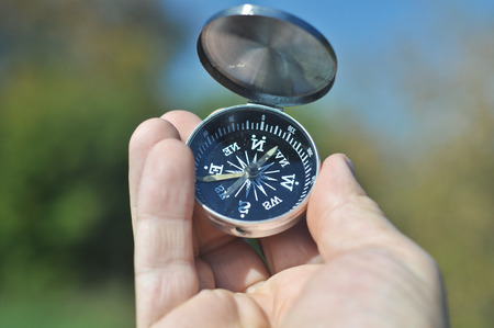 not open: The compass in the palm of your hand. Open the compass helps not to get lost on a walk. Stock Photo