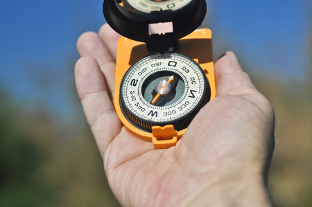 astray: The compass in the palm of your hand. Open the compass helps not to get lost on a walk. Stock Photo