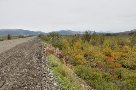 Soil highway in Yakutia. Cloudy landscape on a route Yakutsk - Magadan. Russia. mountains