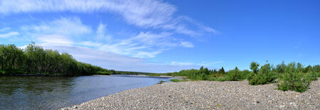 rifts: Panorama of the Northern Ural river under the sun. Pebble beach, transparent rifts and bushes.
