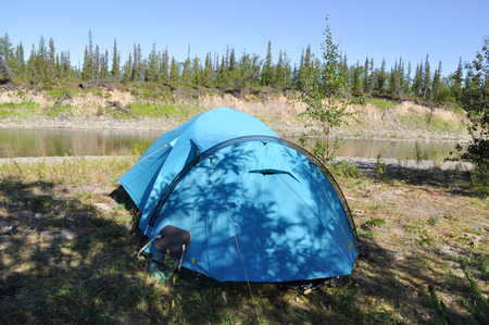 Camping tent on the shore of a mountain river. Polar Ural, Komi Republic, Russia. Stock Photo