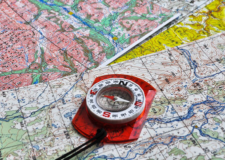 Map and compass. The magnetic compass is located on a topographic map. Archivio Fotografico