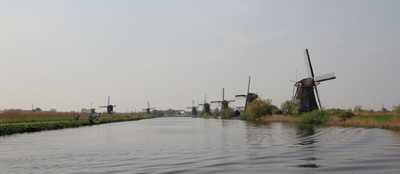 holland landscape: Dutch landscape with windmills. Gloomy panorama of gray water channel and windmills in Holland.