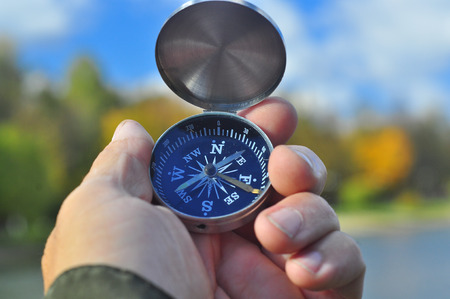 Compass and hand. The magnetic compass is in his hand on the autumn landscape.